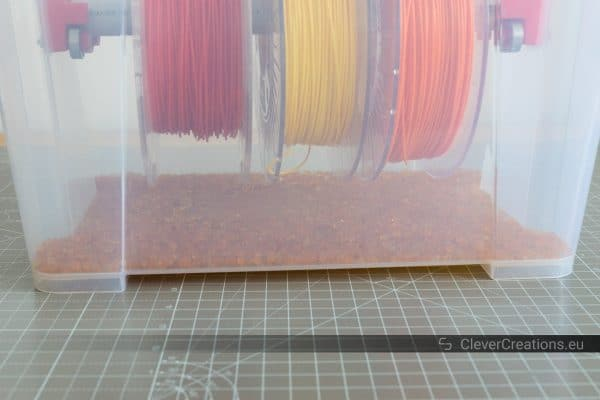 An IKEA SAMLA filament storage box with a layer of reusable silica gel beads to keep the filament dry.