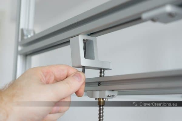 A hand using a hex key to tighten the bolts on a grey 3D printed component that is mounted to aluminium extrusion.