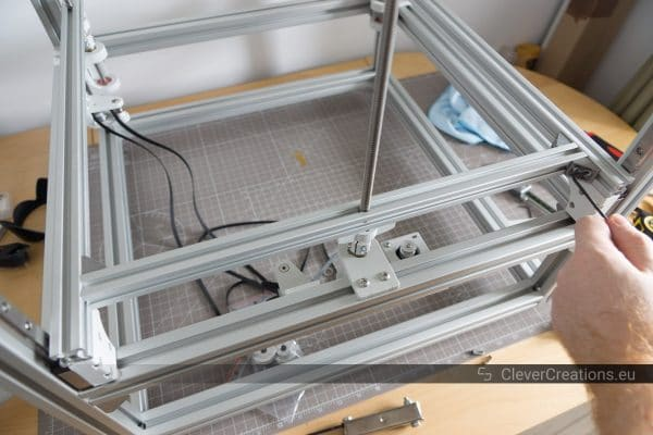 A hand using an allen key to tighten bolts on the Z carriage of a 3D printer.