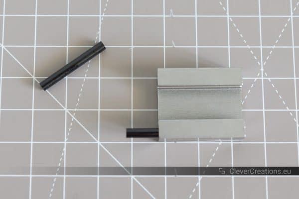 A metal MGN12H carriage block component with PTFE inserts.