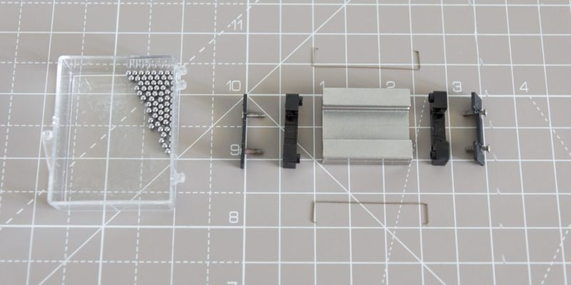 A fully disassembled MGN12H linear rail carriage with all components laid out on a surface.