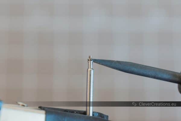 A spring bar pin for watch straps held in place by a clamp, while a spring bar tool is placed in the groove of the pin.