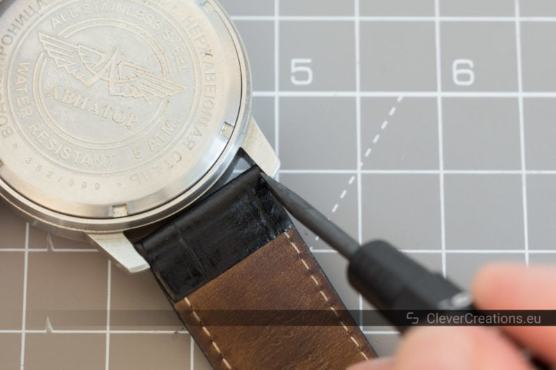 A spring bar tool being used to remove the spring bar pin of a black leather watch strap of an Aviator watch.