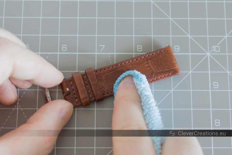 A hand using a microfiber cloth to wipe sweat and dirt of off a brown leather watch band.