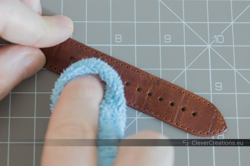 A hand using a cloth to clean a leather watch strap with circular rubbing movements..