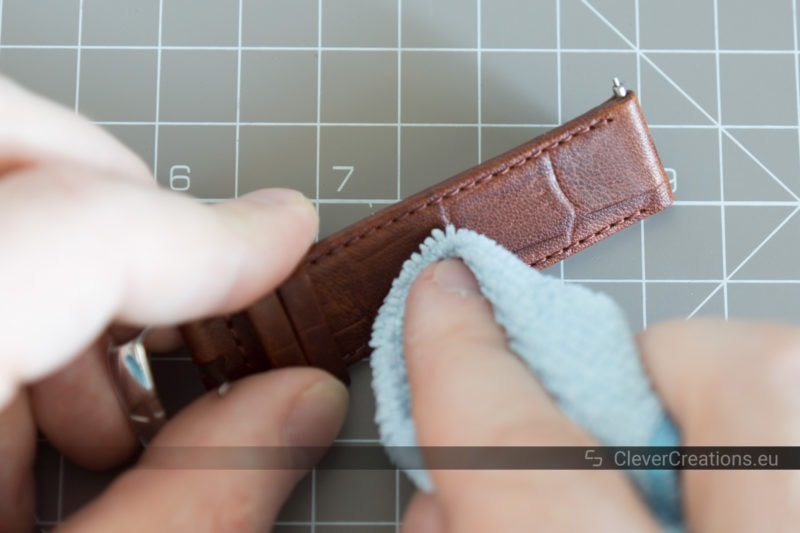 A microfiber cloth being used to wipe soap residue from a brown watch strap.