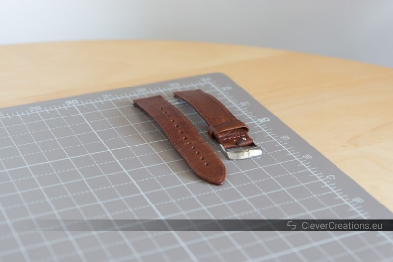 A brown leather watch band resting and air-drying on the corner of a desk.