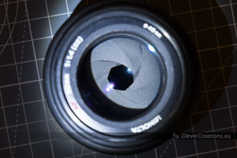 A close-up of the aperture blades in a camera lens. Visible on the blades are a couple of dark spots caused by oil.
