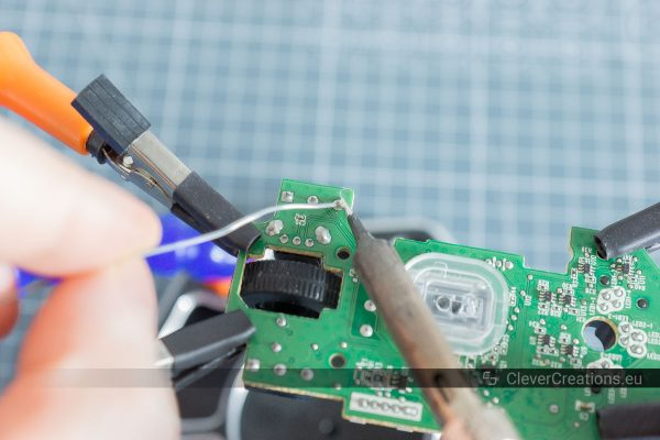 A hand adding solder to the solder joint of a microswitch on the underside of a circuit board.