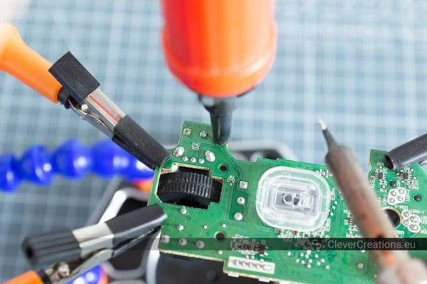 A desoldering pump and a soldering iron being used to remove solder from a solder joint.