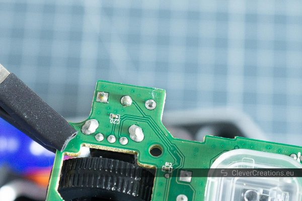 A bare microswitch pin on the underside of a circuit board with the solder removed from the solder joint.