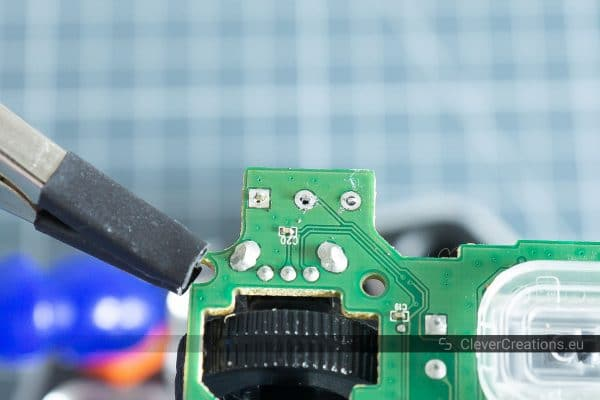 Three bare pins on the underside of a circuit board, without solder joints and solder.