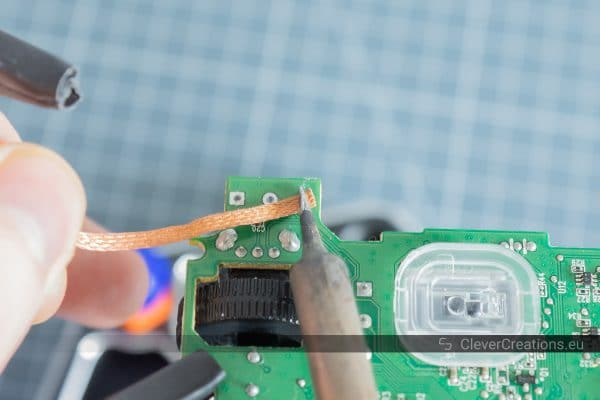 Desoldering braid/solder wick being used to remove solder from solder pads on the underside of a circuit board.