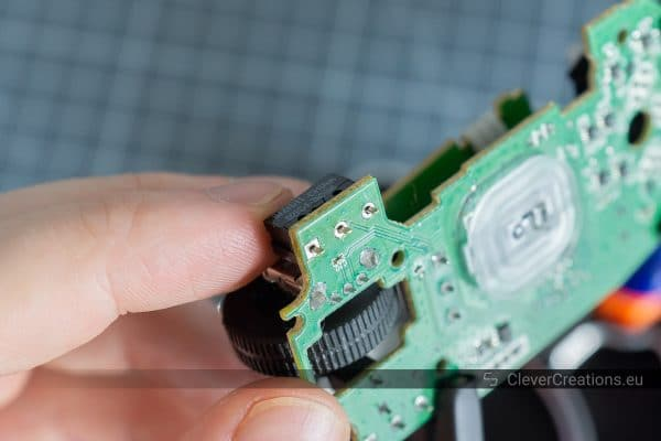 A hand inserting a D2FC-F-7N microswitch through holes in a circuit board for a computer mouse.