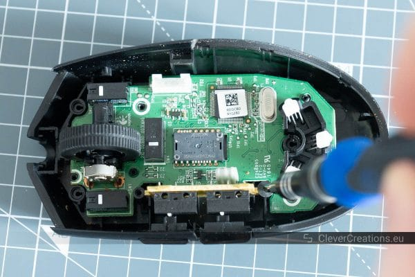 A screwdriver screwing a screw into place in a Logitech G Pro computer mouse.