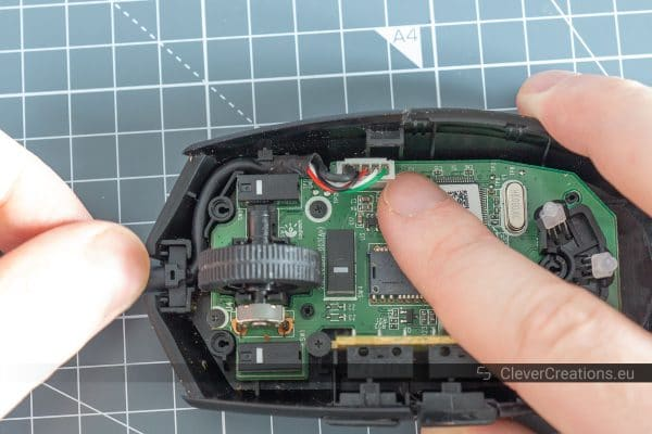 A hand plugging a USB cable into a computer mouse.