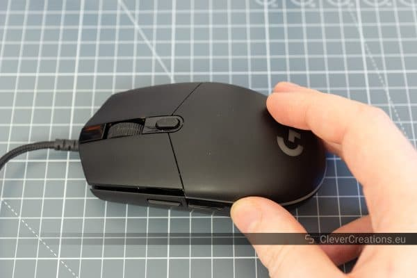 A hand placing the top plastic cover of a mouse casing on top of the bottom half of the casing.