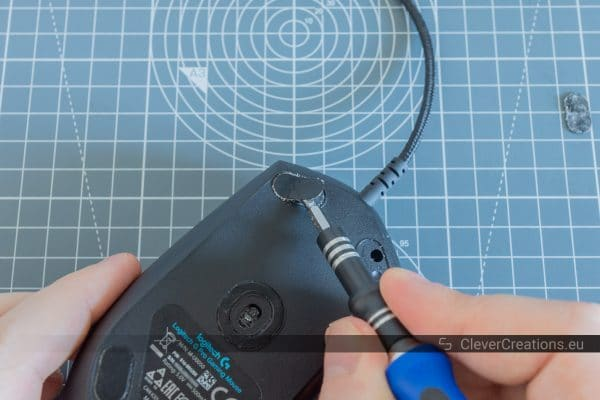 A hand holding a screwdriver to remove a foot from the bottom of a flipped over gaming mouse.