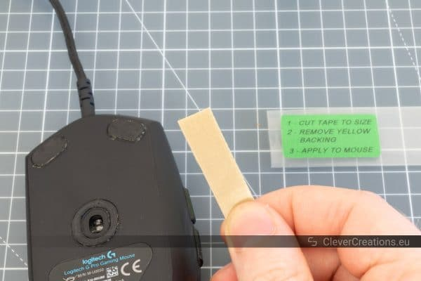A hand holding a piece of PTFE mouse tape in front of a Logitech gaming mouse.