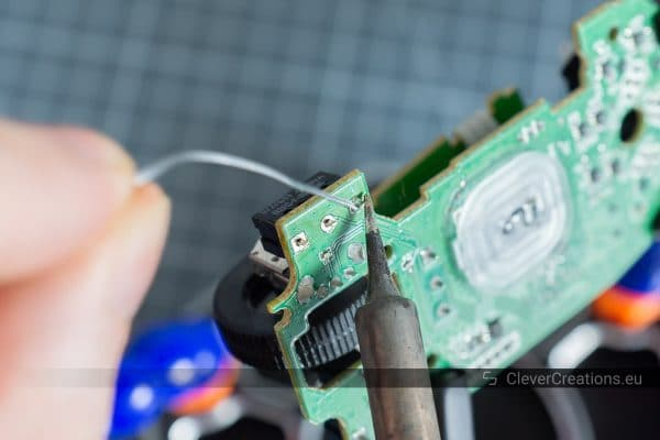 A soldering iron and solder being used to solder a pin of a D2FC-F-7N microswitch to a PCB.