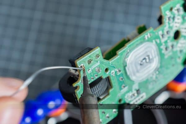 Pins of a microswitch being soldered to the solder pads of a green circuit board.