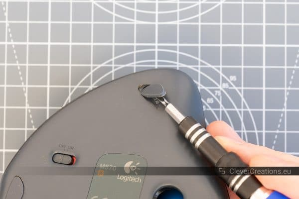 A screwdriver removing one of the feet of a trackball mouse.
