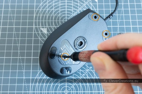 A red screwdriver being used to remove the screws from the bottom of a Logitech G Pro mouse.