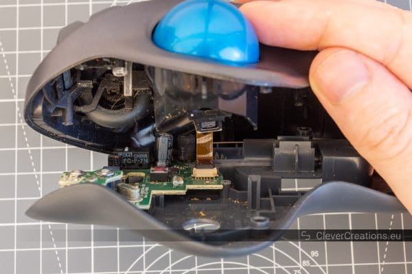 A view of the circuit board and cables of a Logitech M570 trackball that is being held open.
