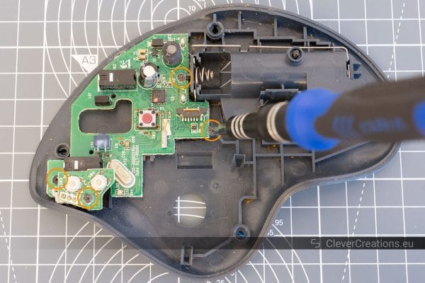 A screwdriver unscrewing a screw on a trackball circuit board, with 4 circled screws.