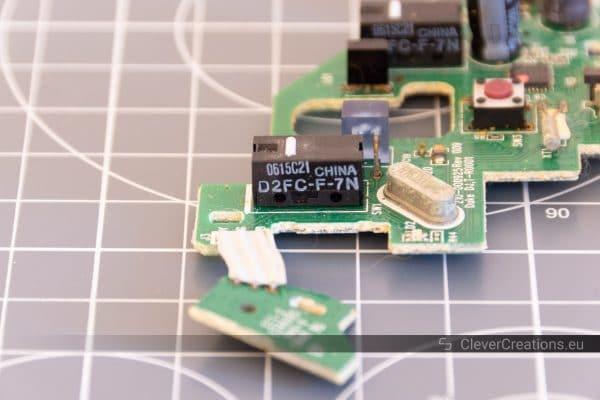 A close-up of a D2FC-F-7N microswitch on a PCB on a desk cutting mat.