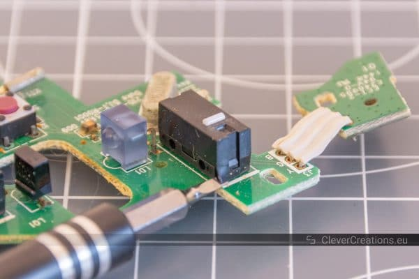 A tiny flathead screwdriver being used to remove the lid of a mouse microswitch.