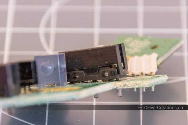 A macro-shot of a D2FC-F-7N microswitch on a PCB with its lid partially lifted off.