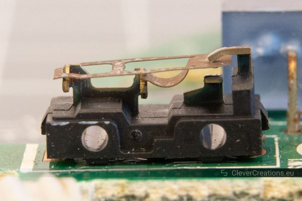 A macro-shot of the interior of a microswitch with a corroded copper spring mechanism.