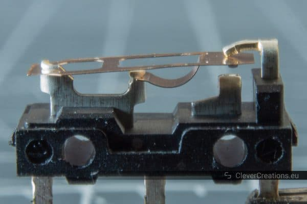 A D2FC–F–7N microswitch without its top cover, with the copper spring visible.