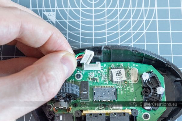 A hand unplugging a USB cable from the PCB of a Logitech G Pro wired mouse.