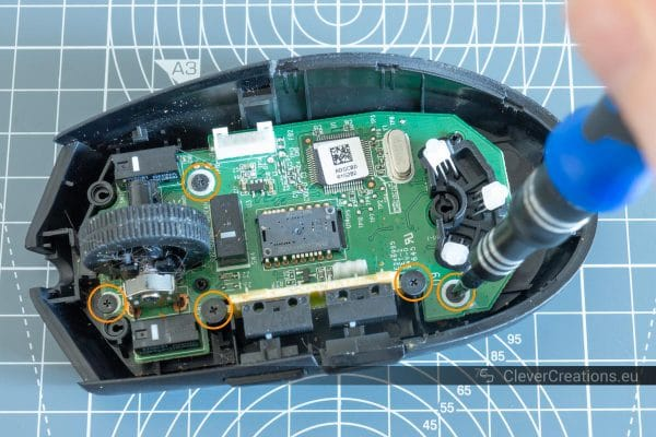 A screwdriver being used to unscrew a screw from a circuit board inside of a mouse, with 5 circled screws.