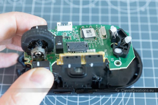 A hand removing the PCB from the plastic casing of a mouse.