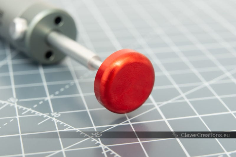 A close-up of a red plunger button on a desoldering pump.