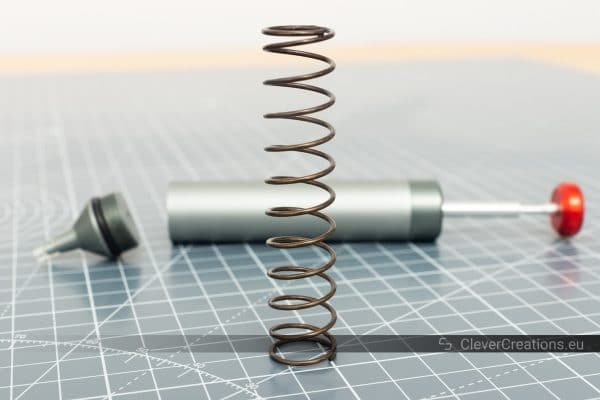 A large spring made from piano wire in front of a partially disassembled Engineer SS-02 solder sucker.