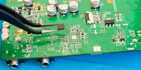 Close-up of a pair of tweezers lifting a desoldered IC from a circuit board.