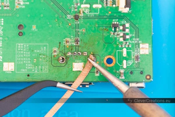 A soldering iron being held on top of desoldering braid to show how to remove solder.