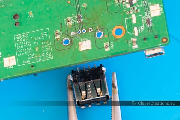 A pair of pliers pulling a desoldered electronic component away from a circuit board.