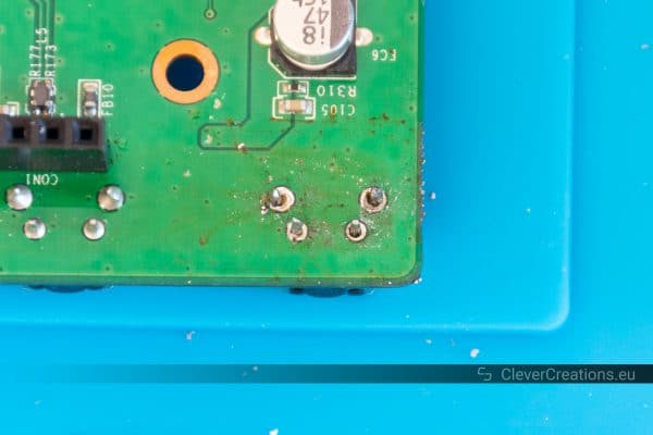 A desoldered button on the solder side of a PCB.