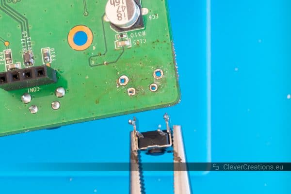 A pair of pliers removing a desoldered button from a PCB.