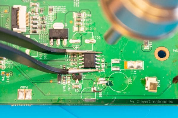 A nozzle of a hot air rework station pointing at a SMD IC that is being held by tweezers.
