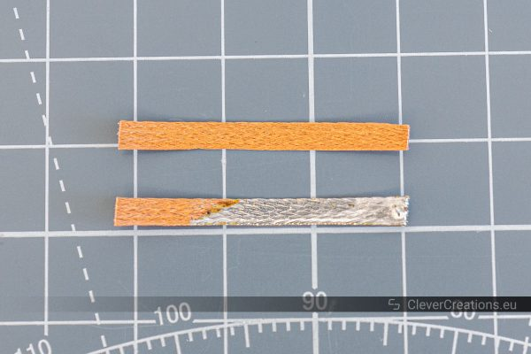 A piece of unused soldering wick next to a piece of used soldering wick.