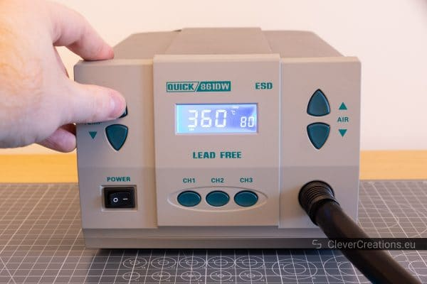 A hand adjusting the temperature setting on a Quick 861DW hot air rework station.
