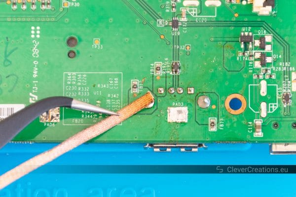 A pair of tweezers holding desoldering braid on top of a solder joint on a circuit board.