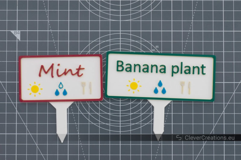 Top view of two coloured DIY plant markers with text and plant care instructions.