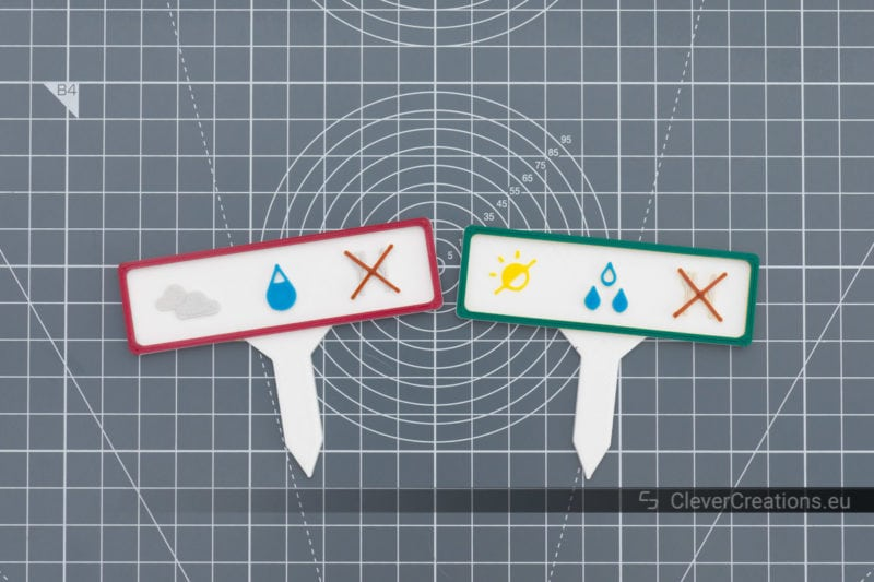 Top view of two coloured DIY garden markers with plant care instruction icons.